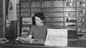 A woman minding a shop with empty shelves and a sign saying 'no matches, no cigarettes, no tobacco. Sorry'